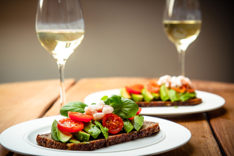 aphrodisiac foods Colorful image of scandinavian rye bread with avocado, tomato, shrimps and basil. Two servings and two glasses of white wine.