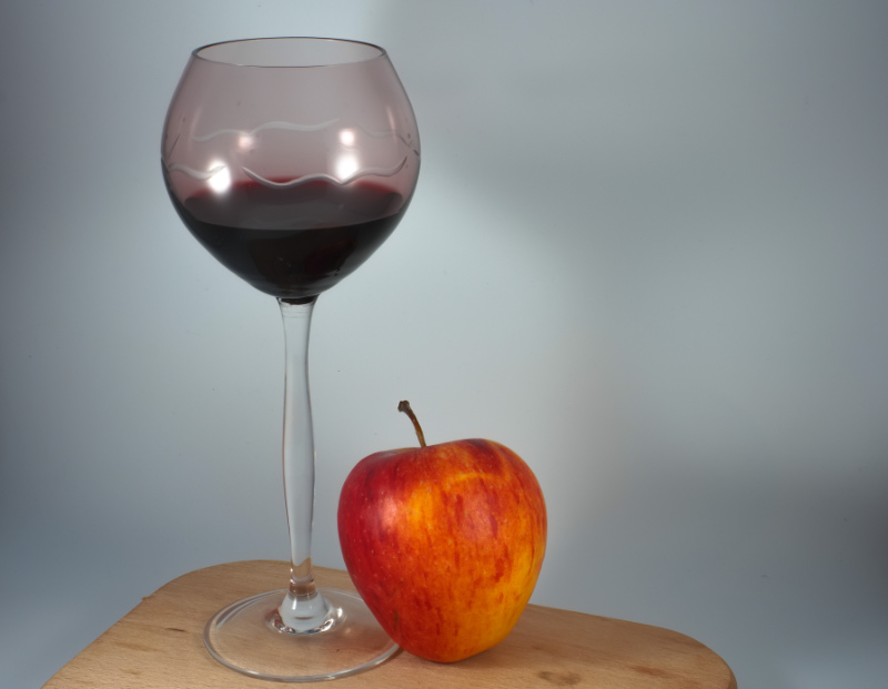 Long glass of pinot noir and red apple