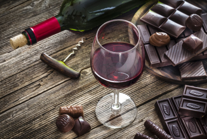 Aphrodisiac foods High angle view of a red wineglass and a selection of various chocolate bars, truffles and pralines shot on rustic wooden table. A wine bottle is at background and complete the composition. Copy space available for text and/or logo. Predominant color is brown. Low key DSRL studio photo taken with Canon EOS 5D Mk II and Canon EF 100mm f/2.8L Macro IS USM.