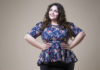 Plus size fashion model in casual clothes, fat woman on beige studio background, overweight female body, professional make-up and hairstyle
