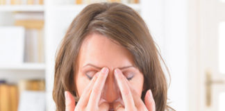 Woman doing EFT on the eye brow point. Emotional Freedom Techniques, tapping, a form of counseling intervention that draws on various theories of alternative medicine.