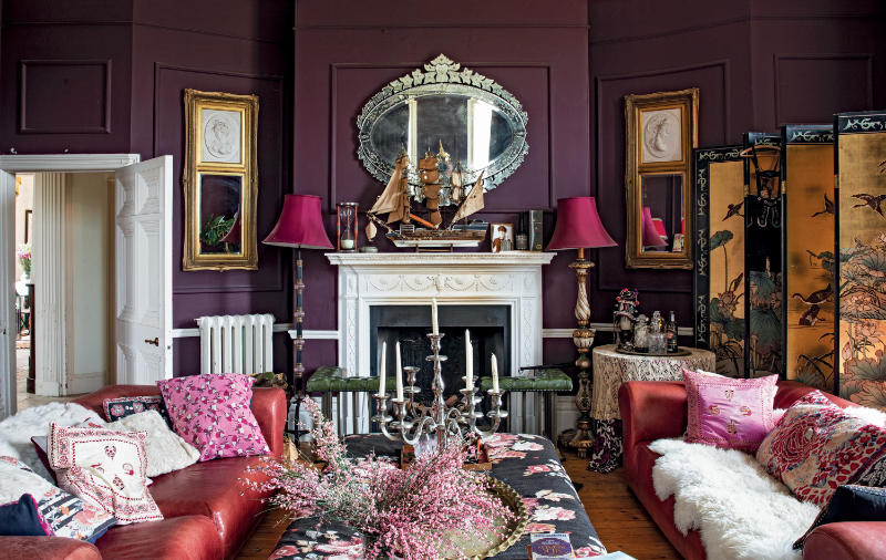 Walls painted in dark aubergine create a cossetting, relaxing atmosphere, brightened by gilded touches from photo frames to a screen found in Hong Kong (Amy Neunsinger/CICO Books/PA)