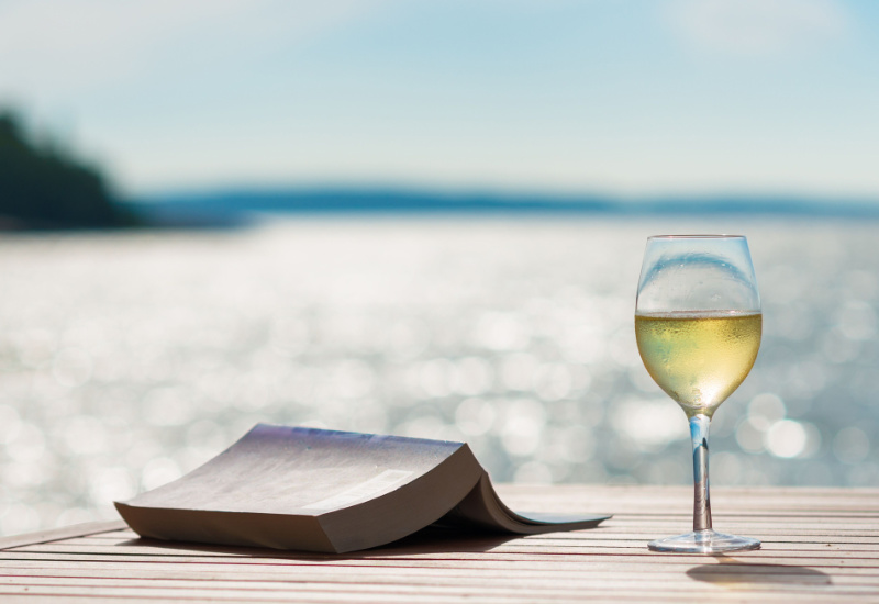 A glass of white wine in front of a book by the glittering sea