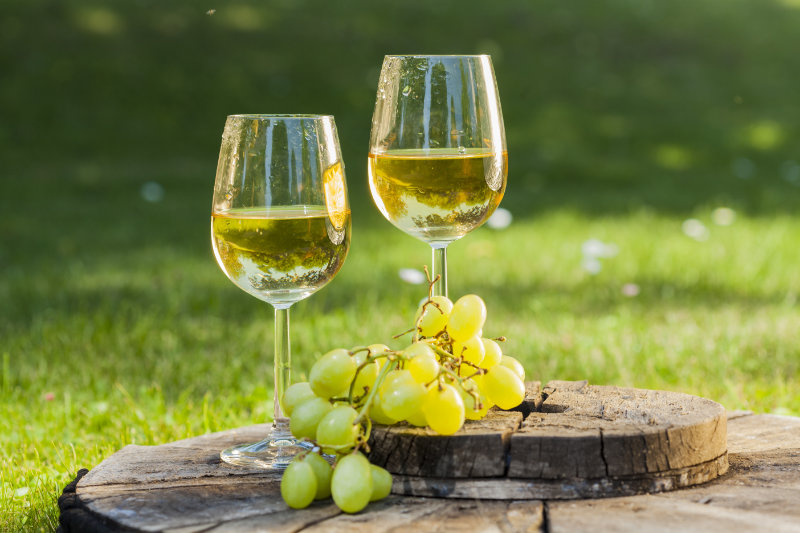 white wine with grapes on old wooden table