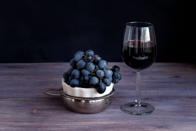 Red wine in wine glass and bunch of dark red purple grapes on wooden board against black background. Toned image. Copy space.