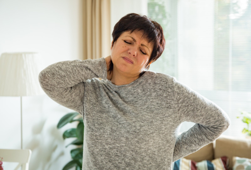 heart attack women Mature woman suffering from backache at home. Massaging neck with hand, feeling exhausted, standing in living room.