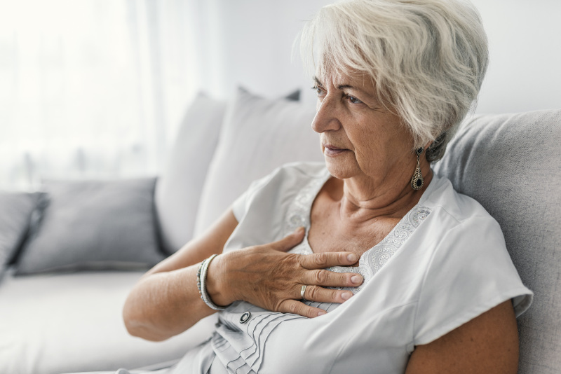 Heart attack symptoms women Female with chest pain. Senior woman suffering from heartburn or chest discomfort symptoms.