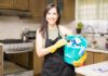 Hiring a cleaner Happy house maid wearing black apron over casuals holding bucket filled with bottles of detergents, spray and disinfectant in kitchen