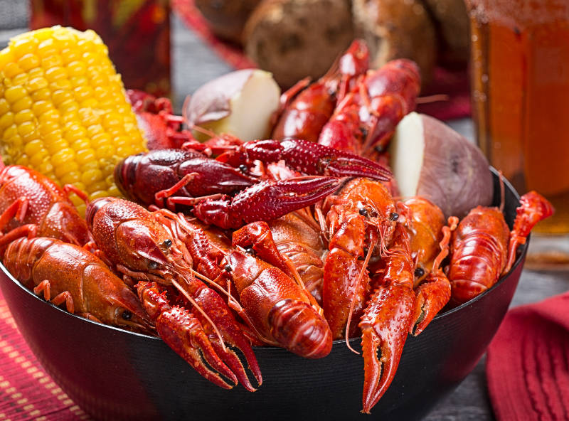 Creole style crawfish boil with corn and potato with a casual, rustic feel.