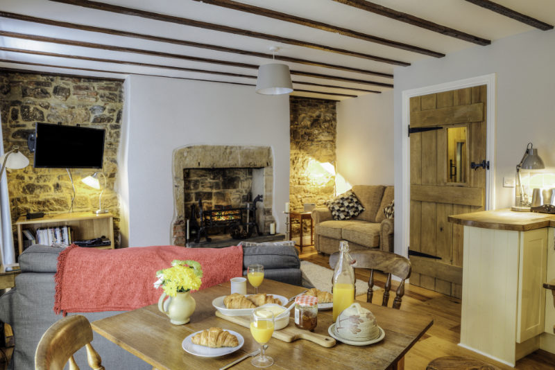 Renting your home Interior shot of a log cabin living room. There are breakfast croissants and juice on the dining table