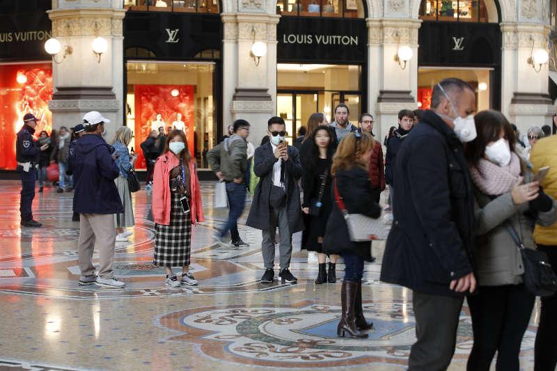 Tourists wearing masks in downtown Milan (Antonio Calanni/PA)