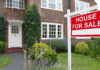 Sell your home fast For sale sign outside a house in an affluent suburb of London