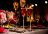 Two Flutes of Rose Champagne on a table with water glasses, candles, and flowers