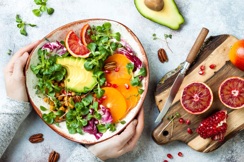 Vegan bloating Girl holding vegan, detox Buddha bowl with turmeric roasted  chickpeas, greens, avocado, persimmon, blood orange, nuts and pomegranate.