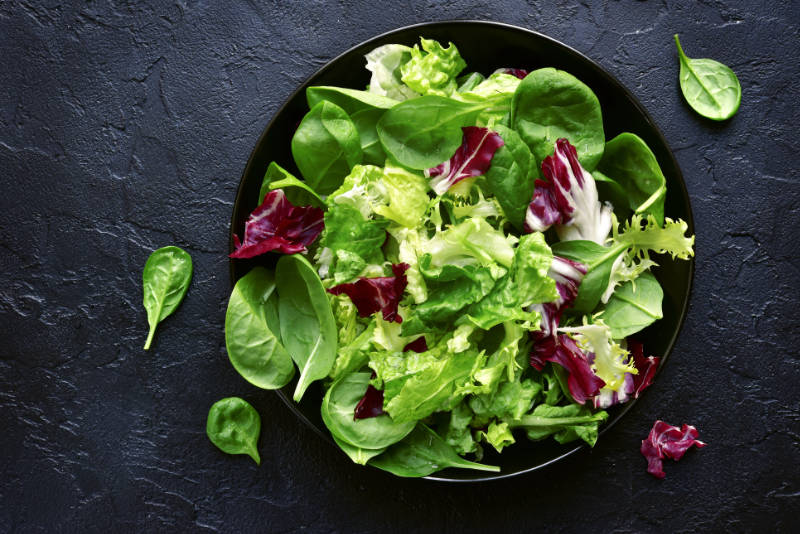 Avoid vegan bloating Mix salad leaves in a black bowl over dark slate, stone or concrete background.