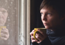 Lonelsome woman drinking cup of coffee by the window of her living room, looking out at snow falling with a sad look on her face. Selective focus with shallow depth of field.