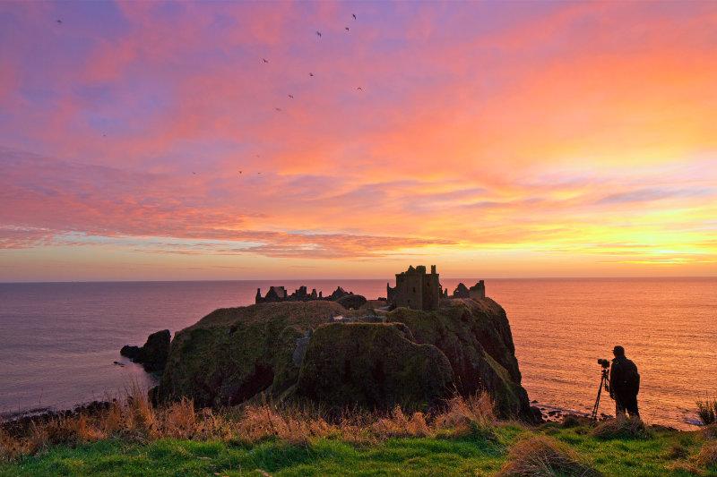 The sun setting over Dunnottar Castle