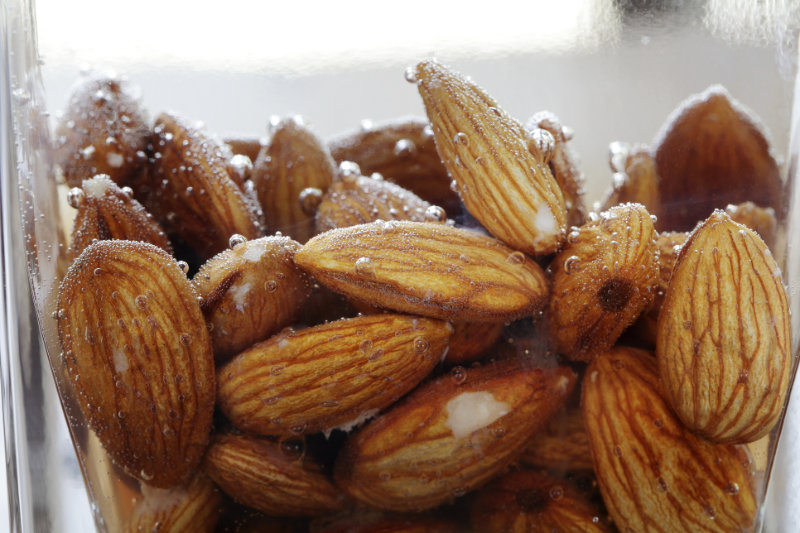 Raw organic fare trade grown almonds soak in water, studio shot isolated on white background