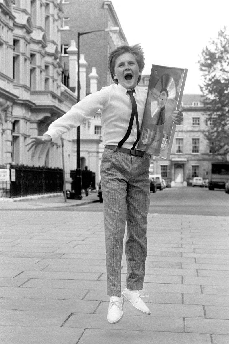 A young Aled Jones jumps for joy on receiving an award.