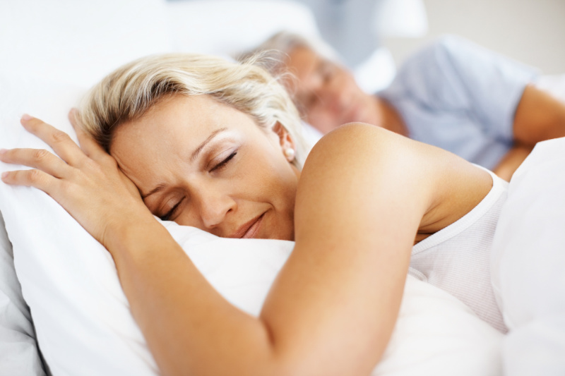 Closeup of mature woman sleeping in bed with man in background