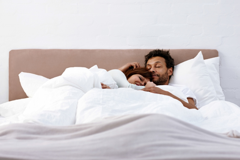 Portrait of interracial couple sleeping together on bed