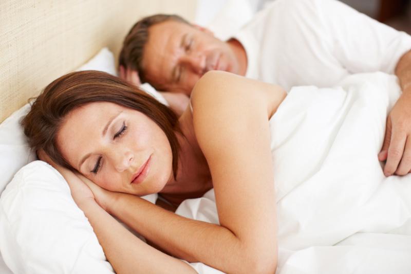 Mature couple sleeping under white linen