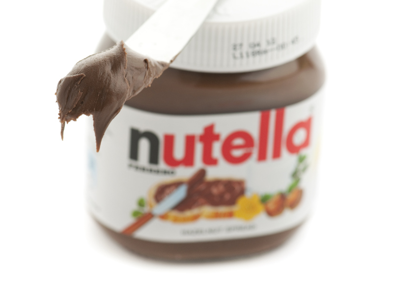 Knife with nutella on it on top of a jar of nutella.