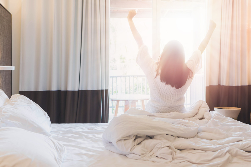 Women are staying in a hotel room after wake up on morning. Open the curtain in the room looking to outside view.