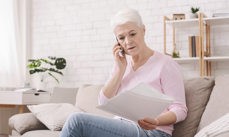 Flood insurance woman on phone looking at documents
