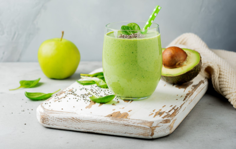 Vegetarian healthy green smoothie from avocado, spinach leaves, apple and chia seeds on gray concrete background.