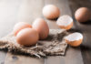 How to crack an egg raw fresh egg on sack and wood background