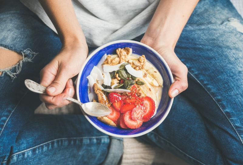 IBS and stress Eating healthy breakfast bowl. Yogurt, granola, seeds, fresh and dry fruits and honey in blue ceramic bowl in woman' s hands. Clean eating, dieting, detox, vegetarian food concept
