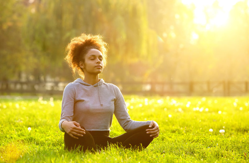 IBS and stress management Young african american woman meditating in nature