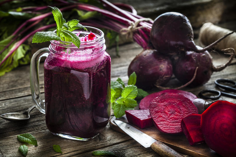 Drinking glass filled with fresh organic beet juice shot on rustic wooden table to help lower blood pressure.