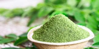 Moringa powder in coconut bowl with original fresh Moringa leaves on wooden background