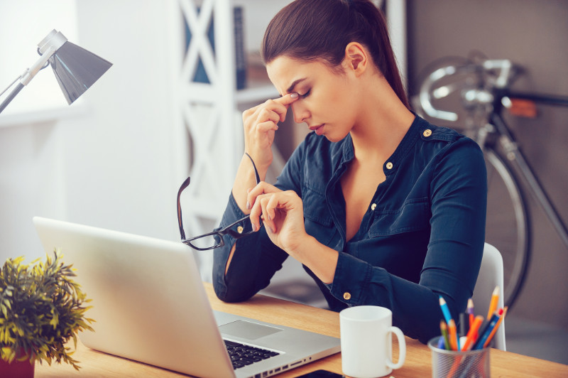 Generic photo of tired-looking woman sat at a desk rubbing her eyes (Thinkstock/PA)