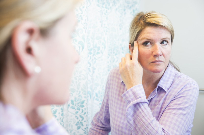 A middle-aged woman looks at her reflection in the mirror.