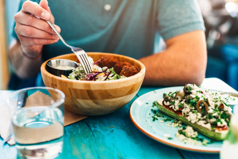 Shot of a young man eating fresh vegan salad with chickpeas balls and sesame sauce on rustic wooden table