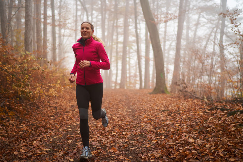 45 year old woman running in autumn forest foggy bad weather conditions cold october or november look
