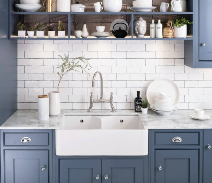 Caple's stainless steel Putney Bridge tap, from around £330 (shown here with a Chepstow sink in a Harptree kitchen), features a classic dual flow bridge design and ceramic valves (Caple/PA)