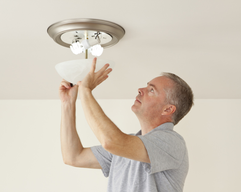 Man changing bulbs in a ceiling light.