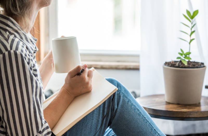A young woman takes a break to do something analog like writing in her journal and drinking tea. This is a healthy practice for those who experience anxiety.