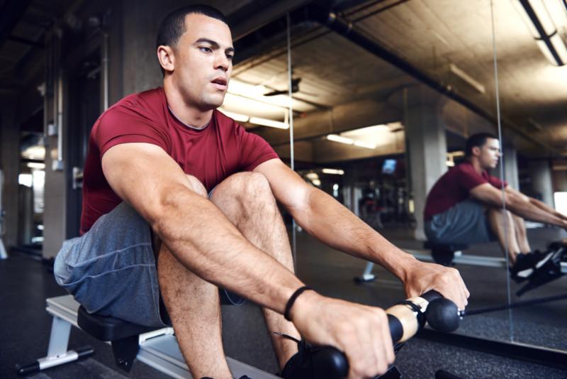 Rowing machine benefits man on rowing machine in gym