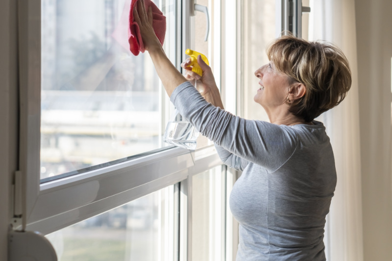 Spring cleaning hacks Senior woman cleaning a windows at home.