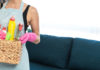 Spring cleaning hacks young adult housewife in apron standing in living room, holding wicker box with detergent and cleaning stuff