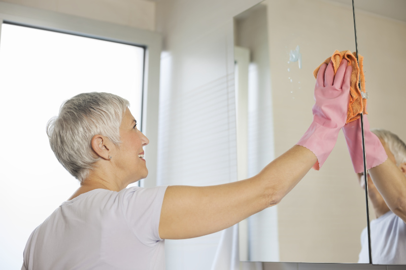 Spring cleaning hacks Mature woman cleaning home, washing bathroom