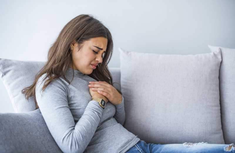 Woman holding hand to spot of pain area, chest pain, Health care concept. Sick woman with indigestion problem, acid reflux or gerd symptoms; woman health care, body care, sickness, pain, acid reflux concept