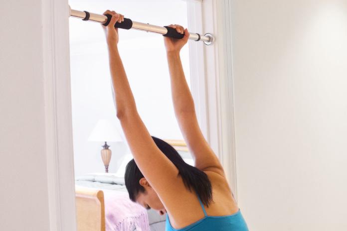 Hispanic woman hanging from pull bars across bedroom doorway.