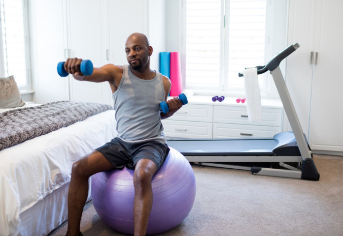 Man exercising with dumbbells on fitness ball in bedroom at home