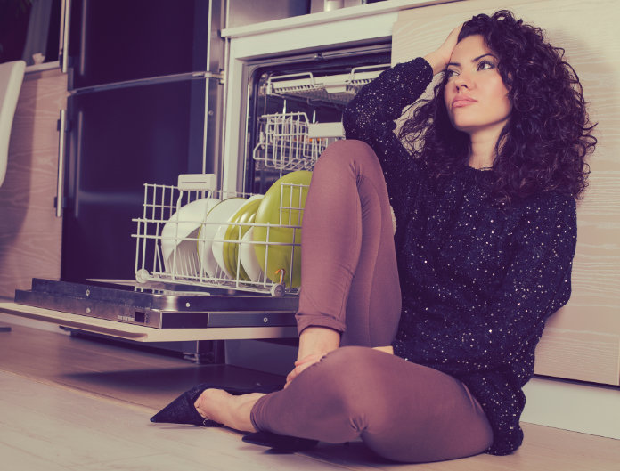 Stressed woman relaxing in the kitchen sitting on a floor